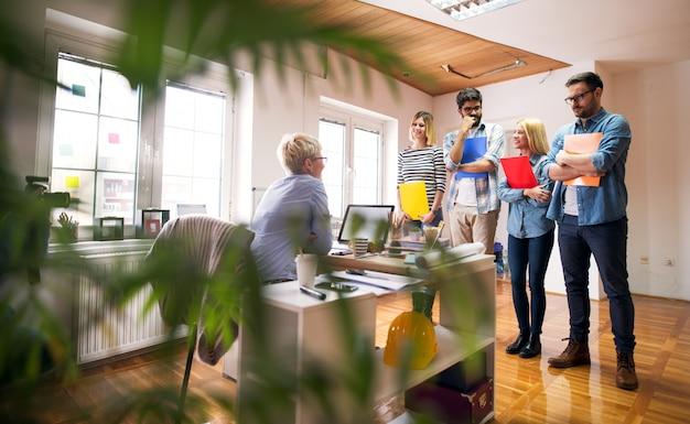 Grupo de cuatro ingenieros nerviosos están en su entrevista de trabajo, de pie frente al escritorio de sus entrevistadores en una oficina muy luminosa