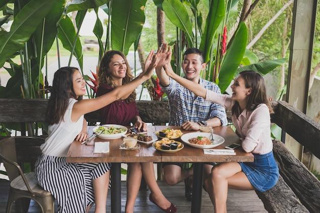 Grupo de cuatro mejores amigos chocando los cinco mientras almuerzan juntos en un café