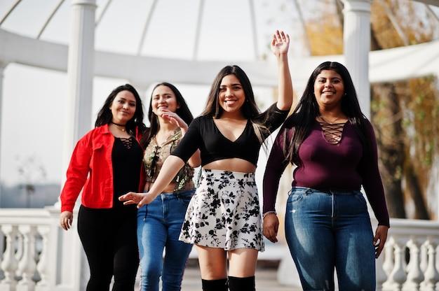 Grupo de cuatro muchachas latinas felices y bonitas de ecuador posó en la calle contra el arco antiguo.