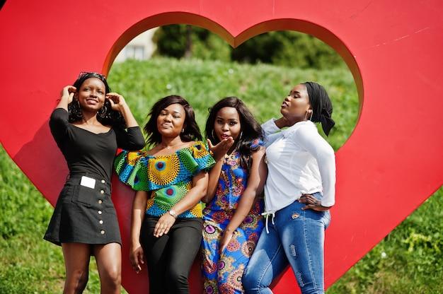 Grupo de cuatro mujeres contra gran corazón rojo al aire libre enviando besos aéreos
