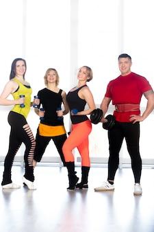 Grupo de culturistas deportivos positivos haciendo peso en el gimnasio