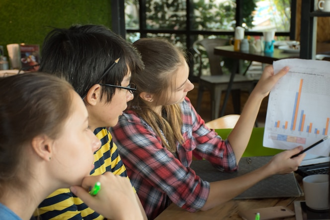 Grupo de amigos adolescentes trabajando y reunión en equipo con informes sobre la mesa de madera