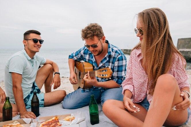 Grupo de amigos atractivos haciendo un picnic, tocando la guitarra en la playa, mientras come pizza