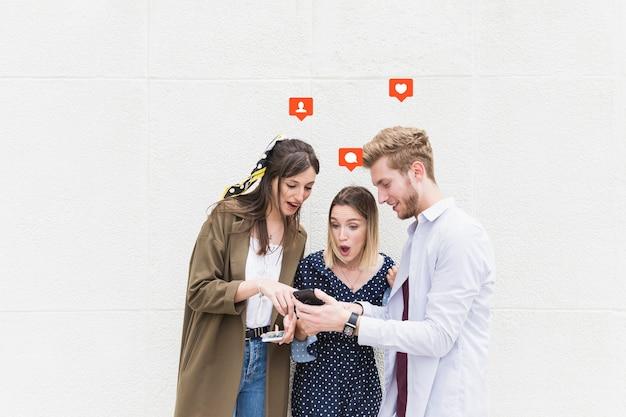 Grupo de amigos de pie cerca de la pared de mensajes de texto en el teléfono móvil