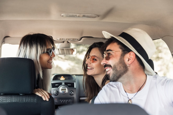Grupo de amigos sentados dentro del coche divirtiéndose