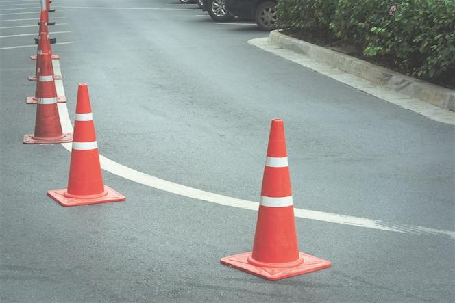 Grupo de conos de tráfico naranja en carretera curva