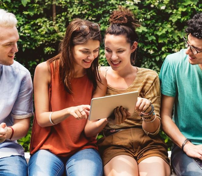 Grupo de diversos amigos que se sientan usando la tableta junto