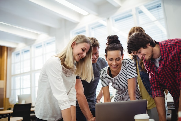 Grupo de ejecutivos de negocios usando la computadora portátil en su escritorio