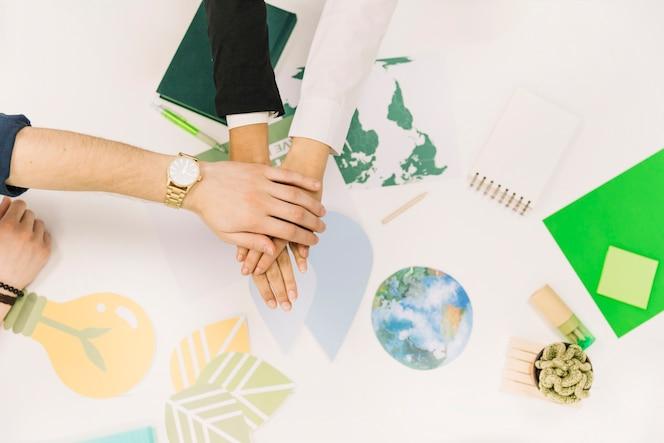 Grupo de empresarios apilando sus manos sobre el escritorio
