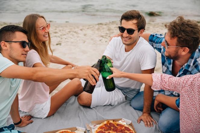 Grupo de mejores amigos haciendo un brindis, bebiendo cerveza mientras se divierten en la playa
