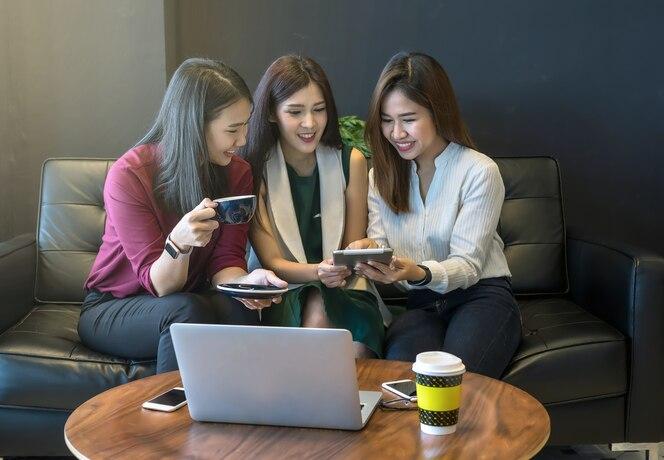 Grupo de mujeres empresarias asiáticas con lluvia de ideas de traje casual