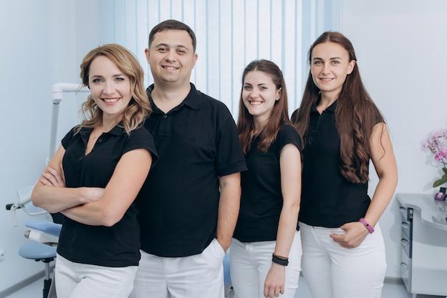 Grupo de dentistas de pie en su clínica y mirando
