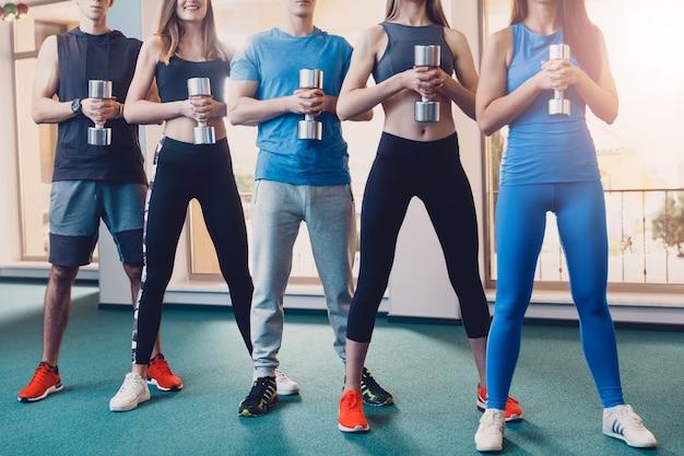 Grupo de deportistas haciendo ejercicio con mancuerna.