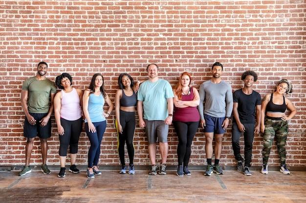Grupo de deportistas por una pared de ladrillos