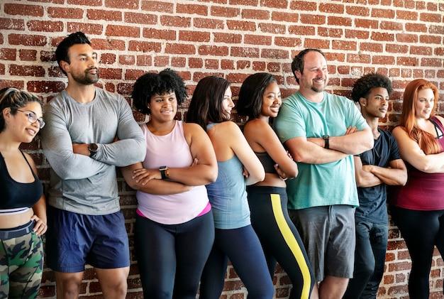 Grupo de deportistas de pie junto a una pared de ladrillos