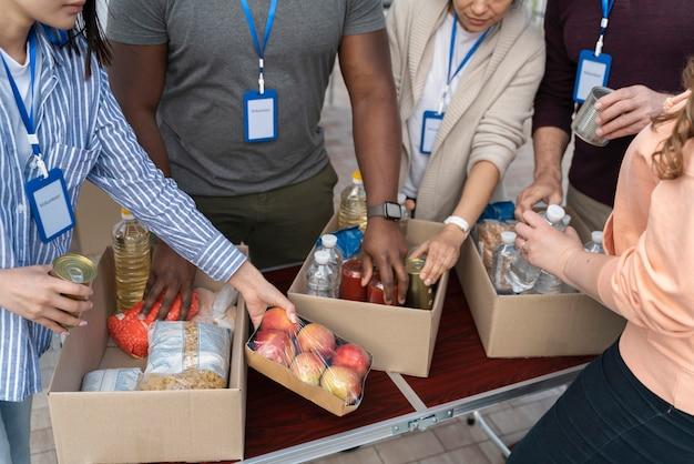 Grupo de diferentes personas voluntarias en un banco de alimentos para personas pobres