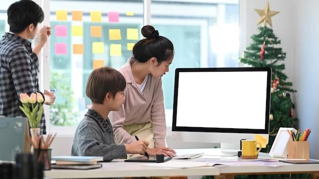 Grupo de diseñador creativo con tableta digital y discutiendo la estrategia empresarial en la oficina.