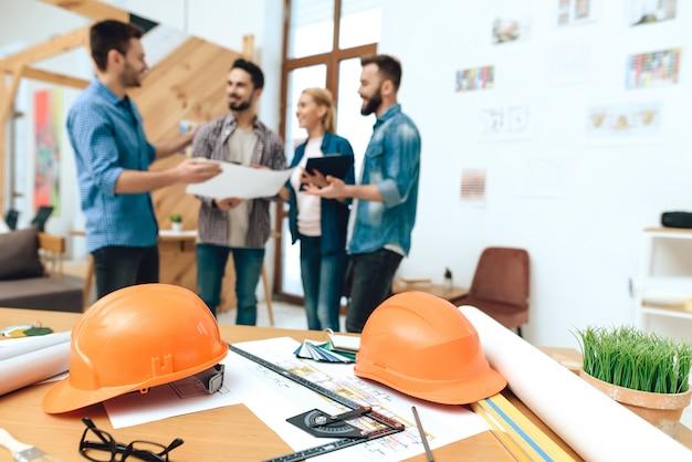 Grupo de diseñadores arquitectos miran planos