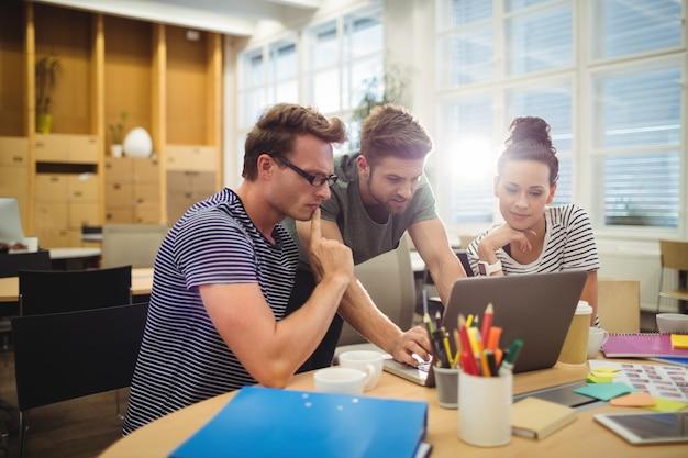 Grupo de diseñadores gráficos que discuten sobre la computadora portátil en su escritorio