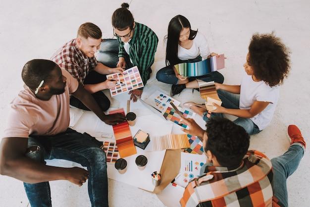 Grupo de diseñadores interraciales es trabajos en oficina.