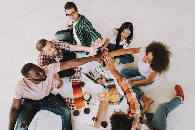 Grupo de diseñadores interraciales están sentados en el piso