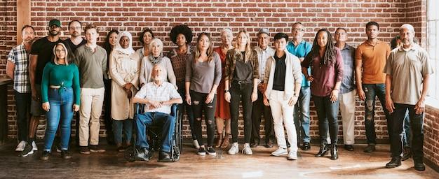 Grupo de diversas personas de pie delante de una pared de ladrillos