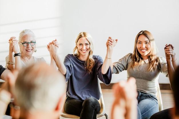 Grupo de diversas personas sosteniendo las manos en el aire