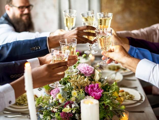 Grupo de diversas personas tintineando copas de vino juntos felicitaciones celebración