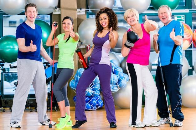 Grupo de diversidad en el gimnasio haciendo deporte en entrenamiento gimnástico