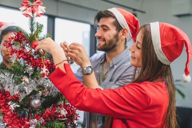 Grupo de diversidad joven creativo feliz celebrando feliz navidad y feliz año nuevo decorando el árbol de navidad en la oficina en la oficina moderna
