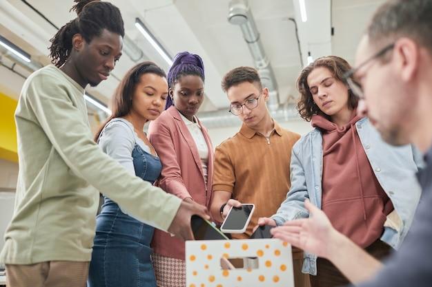 Grupo diverso de adolescentes poniendo teléfonos inteligentes en la caja en el aula sin gadgets en la escuela, espacio de copia