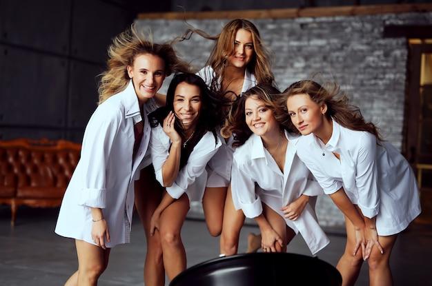 Grupo diverso de amigas disfrutando en una fiesta y riendo. grupo de hermosas mujeres felices divirtiéndose en ropa blanca