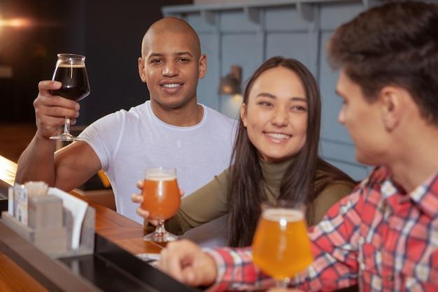 Grupo diverso de amigos bebiendo cerveza en el pub juntos