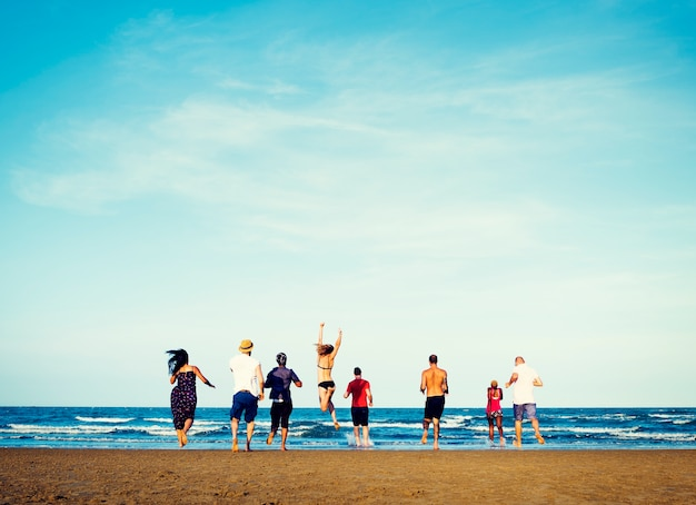 Grupo diverso de amigos corriendo a la playa