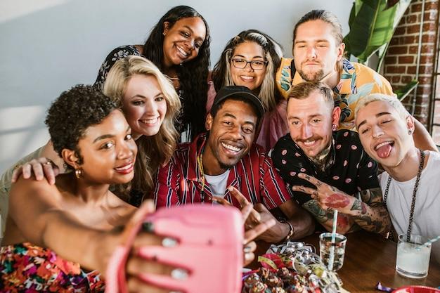 Grupo diverso de amigos tomando un selfie en una fiesta
