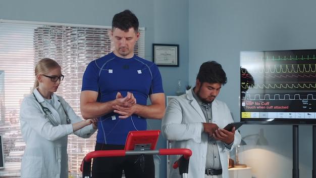 Grupo diverso de científicos deportivos que monitorean la salud física de los atletas.