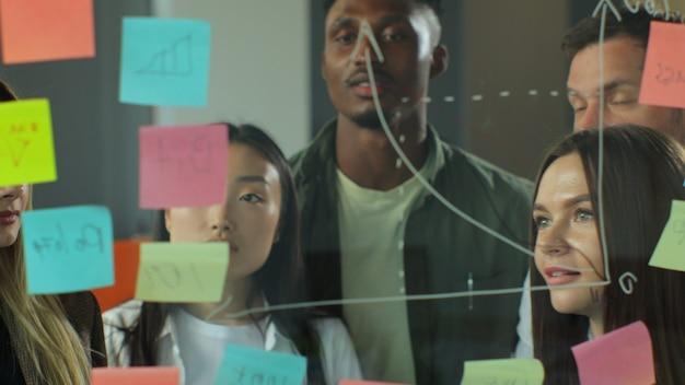 Grupo diverso de compañeros de trabajo que analiza el gráfico de dibujo de estrategia corporativa en una pared de vidrio con notas adhesivas, equipo de negocios multirracial, personas, diseñadores o expertos en marketing, intercambian ideas en reuniones de negocios