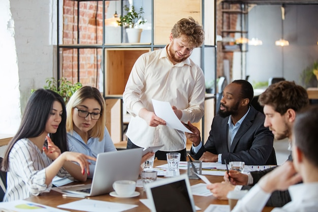Grupo diverso de compañeros de trabajo que tienen una discusión informal en la oficina