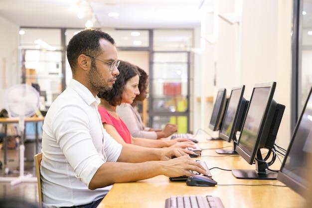 Grupo diverso de estudiantes que toman exámenes en línea.