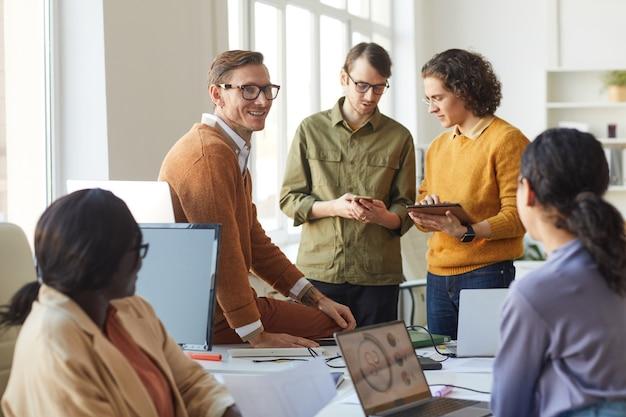 Grupo diverso de jóvenes empresarios que discuten el proyecto de inicio mientras trabajan en la oficina, se centran en el líder del equipo sonriente