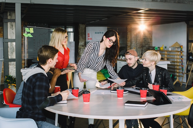 Grupo diverso multiétnico de equipo creativo, gente de negocios informal o estudiantes universitarios en reuniones estratégicas o lluvia de ideas sobre proyectos en la oficina, usando tabletas. concepto de inicio o trabajo en equipo.