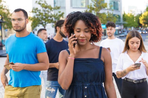 Grupo diverso de personas que usan sus teléfonos inteligentes mientras caminan