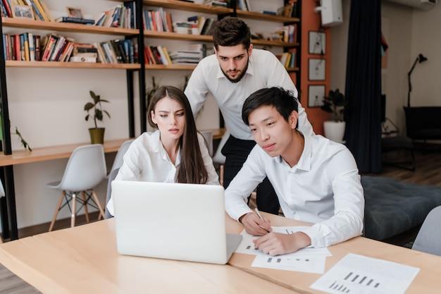 Grupo diverso de trabajadores de oficina milenarios que trabajan con una computadora portátil en los negocios
