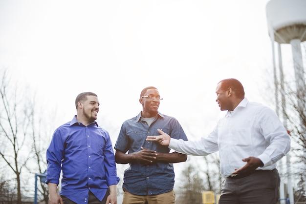 Grupo de diversos amigos varones hablando entre sí y sonriendo