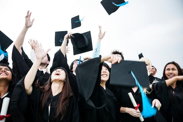 Grupo de diversos graduados tirando gorras en el cielo