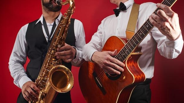 Grupo de dos músicos, banda de jazz masculina, guitarrista y saxofonista en trajes clásicos improvisan en instrumentos musicales en un estudio sobre fondo rojo.