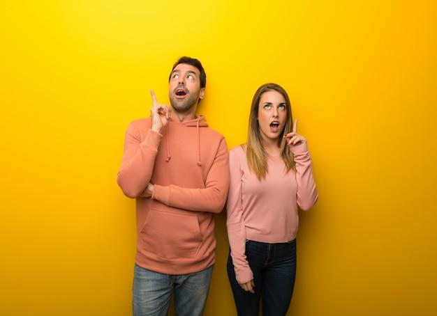 Grupo de dos personas sobre fondo amarillo pensando en una idea apuntando el dedo hacia arriba