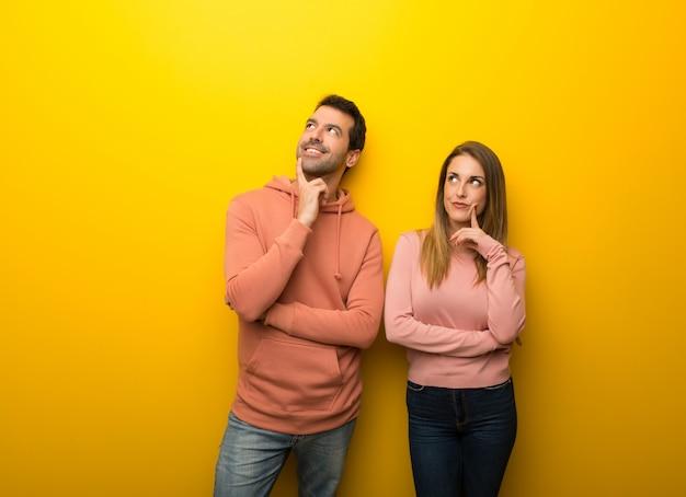 Grupo de dos personas sobre fondo amarillo pensando una idea mientras mira hacia arriba