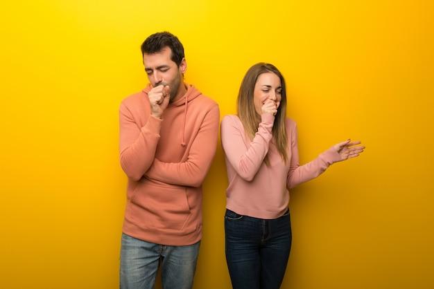 Grupo de dos personas sobre fondo amarillo sufre de tos y se siente mal