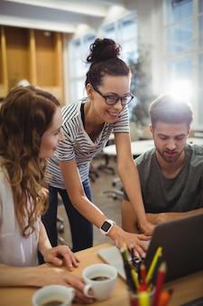 Grupo de ejecutivos de negocios discutir sobre el ordenador portátil en su des